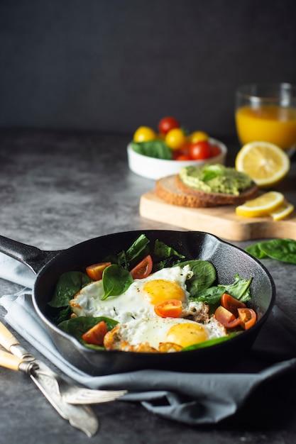 Uova fritte al sole con spinaci, toast di avocado e pomodori freschi, cibo per la colazione sano, Foto Premium