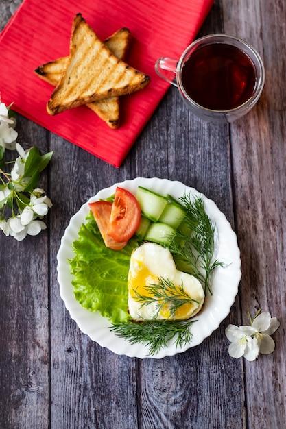 Uova fritte con le fette della lattuga, del cetriolo e del pomodoro su fondo di legno Foto Premium