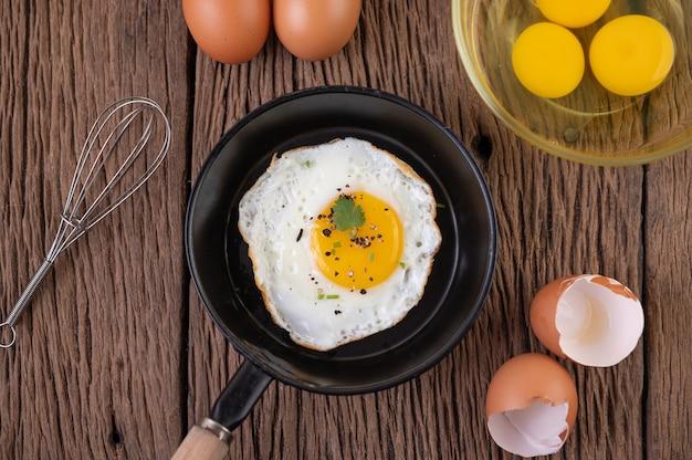 Uova fritte in padella e uova crude, alimenti biologici per una buona salute, ricchi di proteine Foto Gratuite