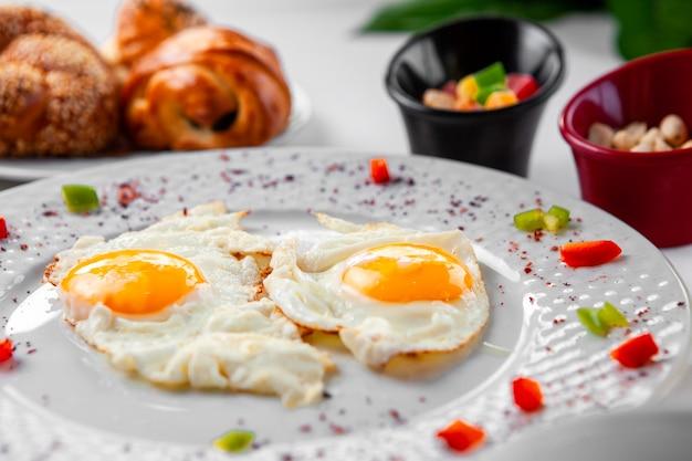 Uova fritte in un piatto con una pasticceria su fondo. vista dall'alto. Foto Gratuite