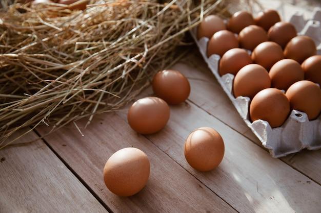 Uova in scatole di carta poste su pavimenti in legno Foto Premium
