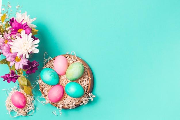 Uova luminose sul piatto vicino al mazzo di fiori Foto Gratuite