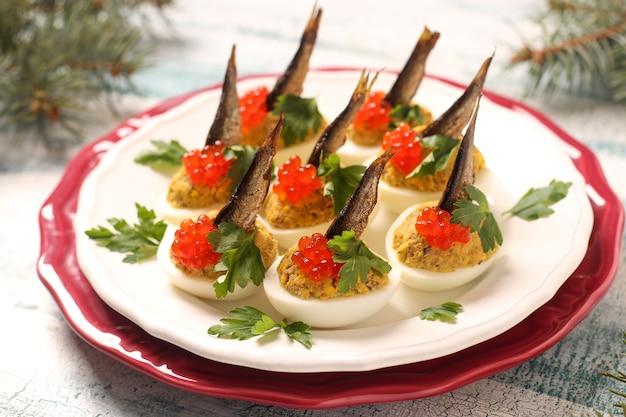 Uova ripiene di spratti e caviale rosso su un piatto bianco. merenda festiva Foto Premium
