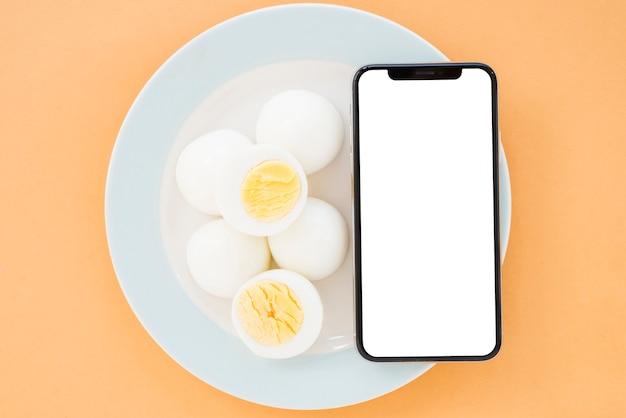Uova sode e telefono cellulare con lo smartphone bianco dell'esposizione di schermo sul piatto bianco ceramico Foto Gratuite