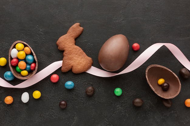 Uovo di cioccolato per pasqua e coniglietto a forma di biscotto con caramelle Foto Gratuite