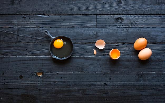 Uovo di gallina su un fondo di legno scuro Foto Premium