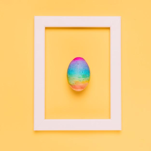 Uovo di pasqua di colore dell'arcobaleno dentro la struttura bianca del confine su fondo giallo Foto Gratuite