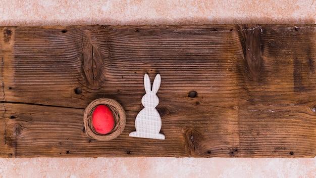 Uovo di pasqua nel nido con coniglio sul tavolo Foto Gratuite