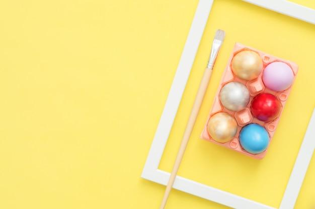 Uovo di pasqua variopinto di vista superiore piana di disposizione dipinto in composizione in colori pastello con il pennello su giallo Foto Gratuite