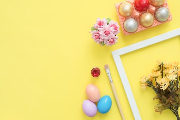 Uovo di pasqua variopinto di vista superiore piana di disposizione dipinto nei fiori della composizione e della molla di colori pastelli Foto Gratuite