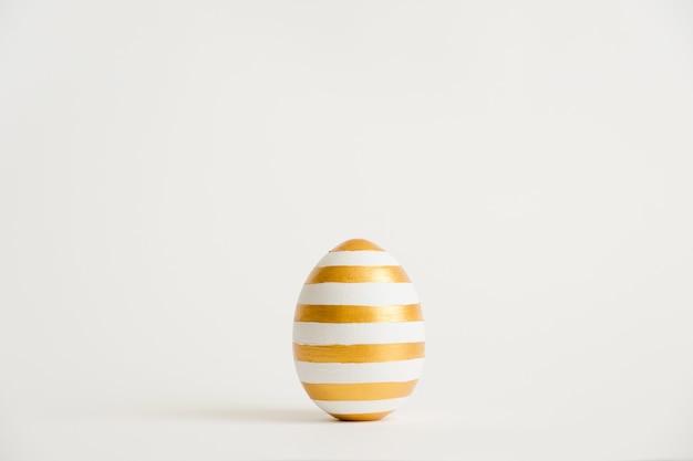Uovo dorato di pasqua con patternd a strisce isolato su fondo bianco Foto Premium