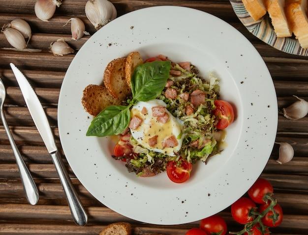 Uovo fritto di vista superiore in un piatto bianco con insalata verde Foto Gratuite