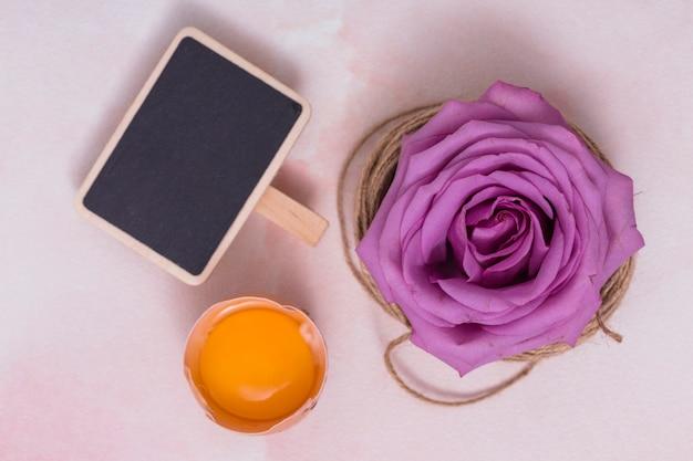 Uovo rotto con tuorlo, lavagna e fiore Foto Gratuite
