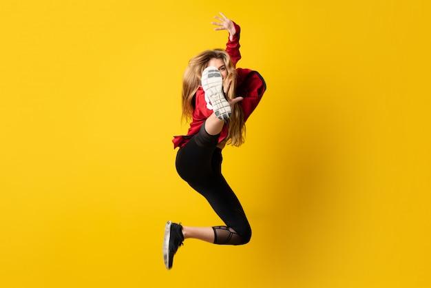 Urban ballerina che danza sopra giallo isolato e saltando Foto Premium