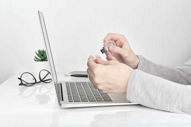 Usb d'apertura della persona accanto al computer portatile, concetto del lavoro d'ufficio Foto Premium