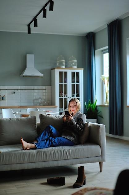 Uso della donna dello smartphone la sera a casa mentre si posa sul divano Foto Premium