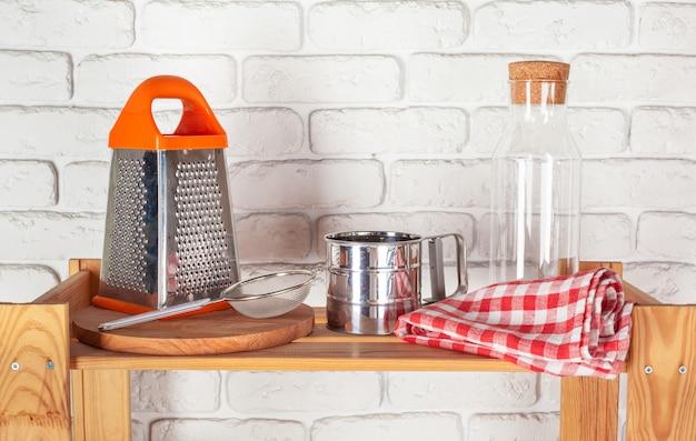 Utensili da cucina e stoviglie sulla mensola in legno Foto Premium