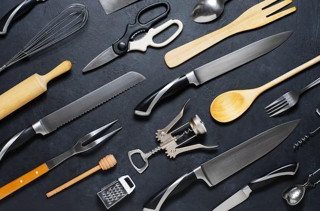 Utensili da cucina in legno e metallo. strumenti per cucinare. sfondo scuro disteso Foto Premium