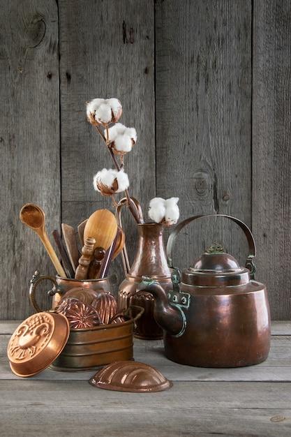 Utensili da cucina in rame vintage su uno sfondo grigio in legno. Foto Premium