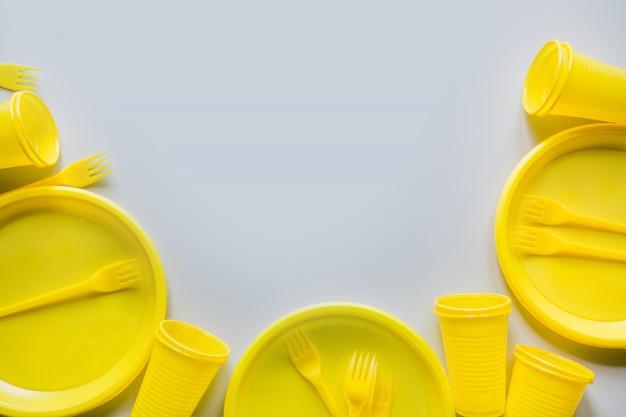 Utensili da picnic gialli monouso, piatti, tazze, forchette su grigio. Foto Premium