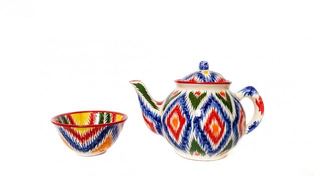 Utensili tradizionali dell'uzbeco - bollitore, ciotola con ornamento ikat su bianco, isolato Foto Premium