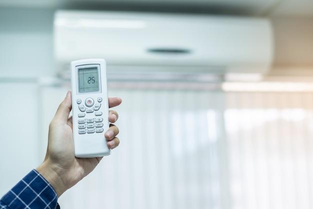 Utilizzando il telecomando per regolare il condizionatore d'aria all'interno della stanza dell'ufficio o della casa Foto Premium