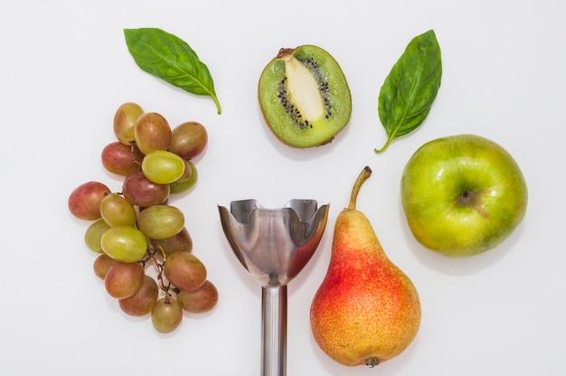 Uva; basilico; kiwi; mela e pera con frullatore elettrico a mano su sfondo bianco Foto Gratuite
