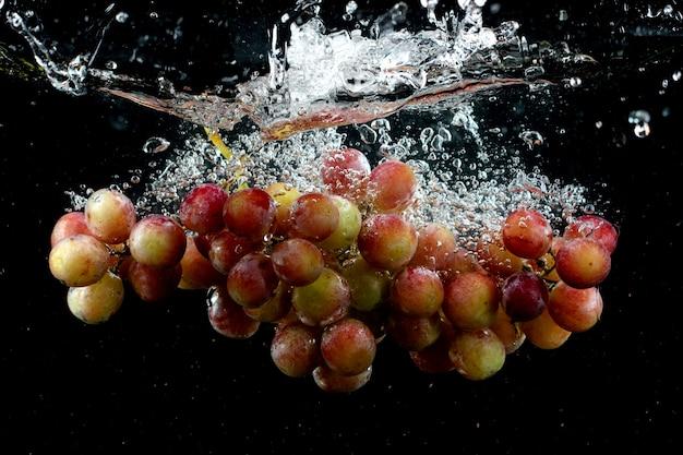 Uva che spruzza nell'acqua in nero Foto Gratuite