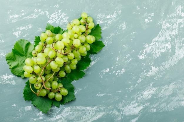Uva con foglie piane giaceva su uno sfondo di intonaco sgangherata Foto Gratuite