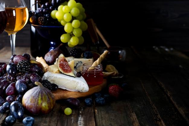 Uva, formaggio, fichi e miele con un bicchiere di vino bianco Foto Premium