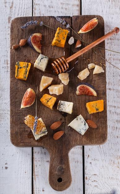 Uva, formaggio, fichi e miele con un bicchiere di vino rosso e bianco su una tavola di legno Foto Premium