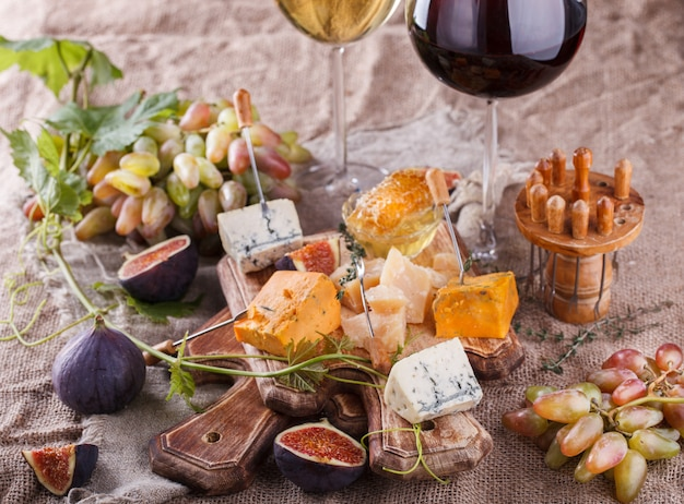 Uva, formaggio, fichi e miele con un bicchiere di vino rosso e bianco Foto Premium