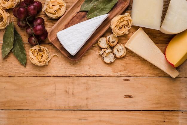 Uva fresca; pasta; formaggio e foglie di alloro sul bancone di legno Foto Gratuite