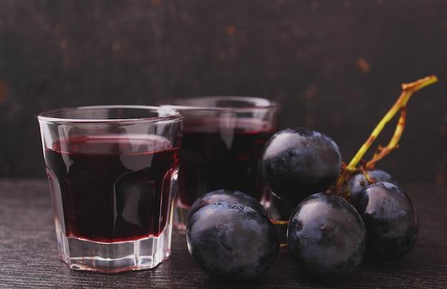 Uva matura, vino rosso e un bicchiere su uno sfondo nero Foto Premium