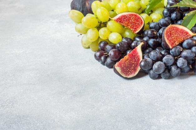 Uva nera e verde, fichi e foglie su un tavolo grigio Foto Premium