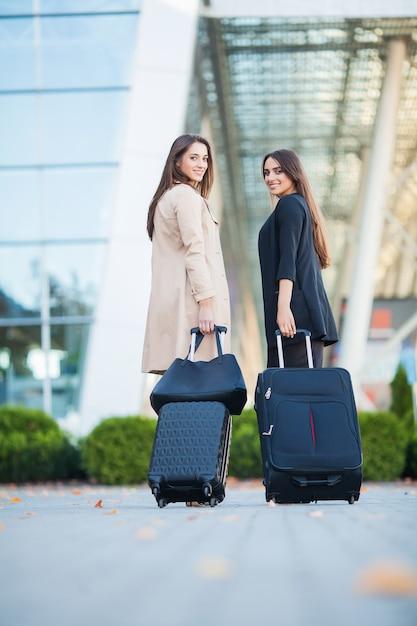 Vacanza. due ragazze felici che viaggiano insieme all'estero, portando i bagagli in valigia in aeroporto Foto Premium
