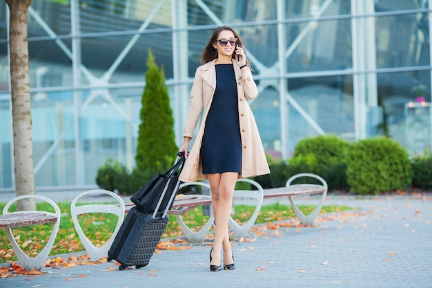 Vacanza. passeggero femminile sorridente che procede all'uscita del cancello che tira valigia attraverso il concorso dell'aeroporto Foto Premium