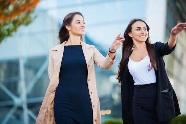 Vacanze, due ragazze felici che viaggiano insieme all'estero, portando bagagli in valigia in aeroporto Foto Premium