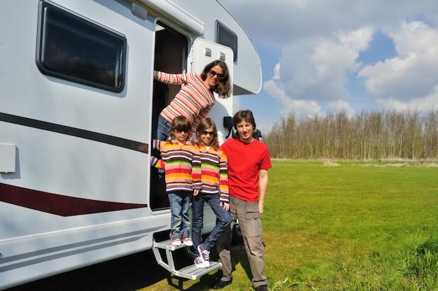 Vacanze in famiglia, viaggi in camper (camper) con bambini, genitori felici con bambini si divertono in viaggio di vacanza in camper Foto Premium