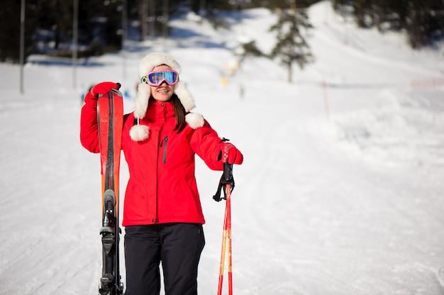 Vacanze invernali e concetto di sport con la donna con gli sci in mano ai piedi della montagna Foto Premium