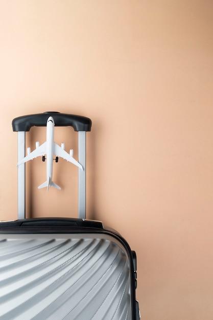 Valigia grigia laica piatta con mini aereo su sfondo pastello. Foto Premium