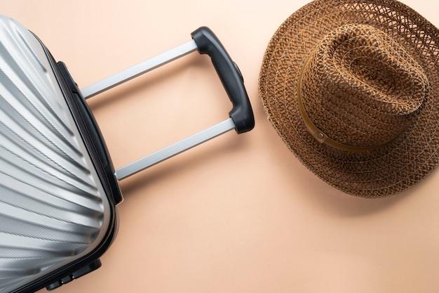 Valigia grigia piatta con cappello marrone. concetto di viaggio Foto Premium
