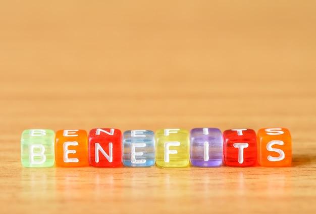 Vantaggi parola composta da blocchi di colori diversi sullo sfondo della tabella Foto Premium