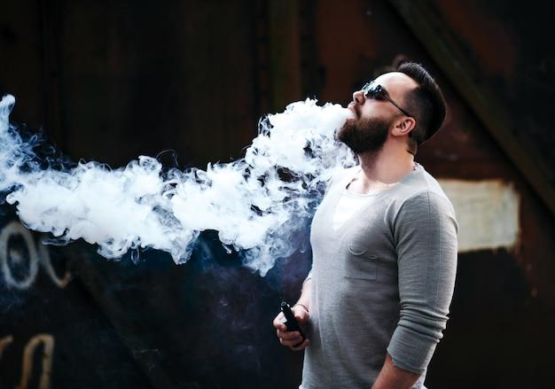 Vaper con la barba in occhiali da sole vaping all'aperto Foto Premium