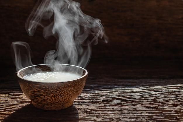 Vapore di mush o riso bollito stile asiatico con fumo in ciotola di legno su sfondo scuro Foto Premium