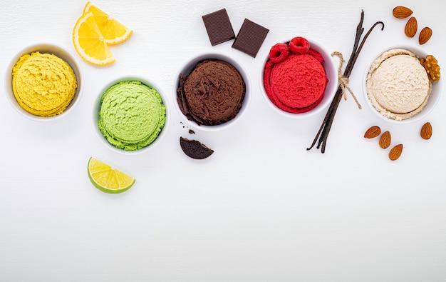 Vari di gelato sapore palla mirtillo, lime, pistacchio, mandorla, arancia, cioccolato e vaniglia istituito su fondo di legno bianco. concetto di menu estate e dolce. Foto Premium
