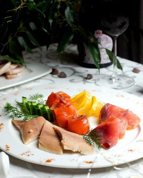Vari filetti di pesce a fette con fetta di limone Foto Gratuite
