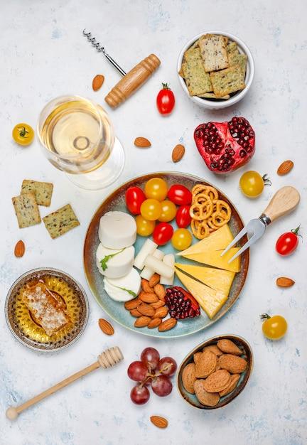 Vari formaggi e piatto di formaggi sul tavolo luminoso con diversi tipi di noci e frutta Foto Gratuite