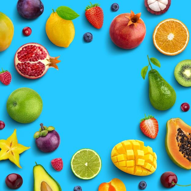 Vari frutti e bacche isolati su sfondo blu, vista dall'alto, layout piatto creativo, cornice rotonda di frutti con spazio vuoto per testo Foto Premium