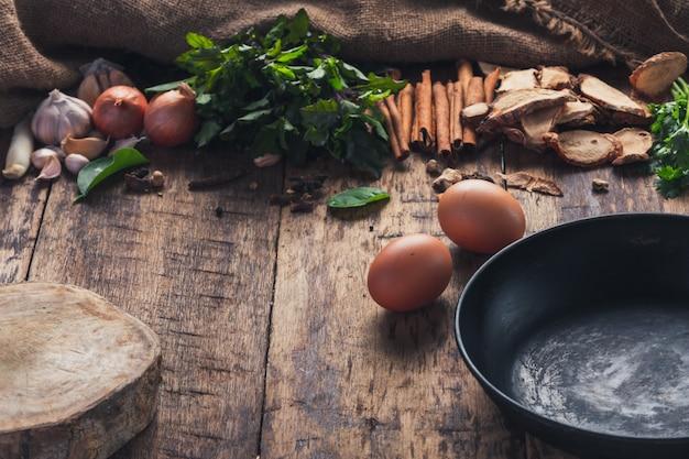 Vari ingredienti utilizzati per preparare il cibo asiatico sono posti accanto alla padella sul tavolo di legno. Foto Gratuite